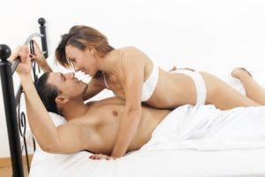 Uomo disteso sul letto con una donna sopra in intimo